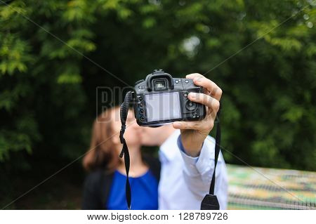 Happy couple making selfie with camera. Lovers kiss and make selfie on camera in park.
