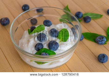 Blueberries with yogurt and mint leafs on wooden table. Yogurt with blueberries and mint. Blueberries with yogurt and mint in transparent bowl. Transparent bowl with yogurt blueberries and mint. Soft focus.