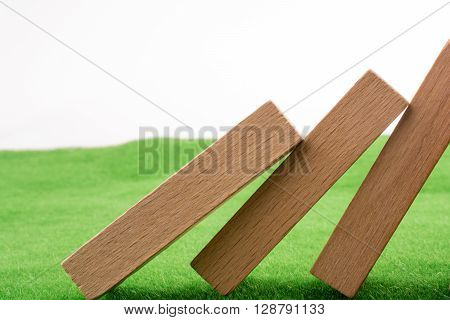 Wooden dominos on green grass on a white background