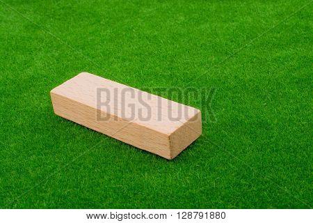 Wooden domino on an artificial green grass