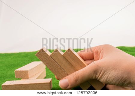 Hand holding Wooden dominos on green grass