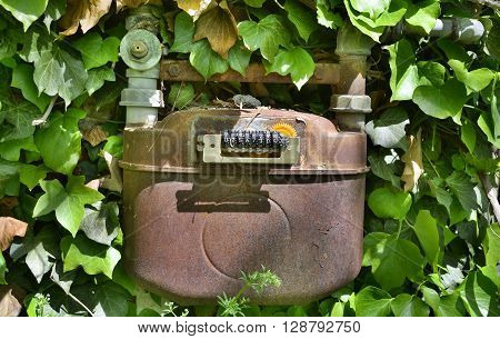 An old disused gas meter on the outside of a derelict Italian building