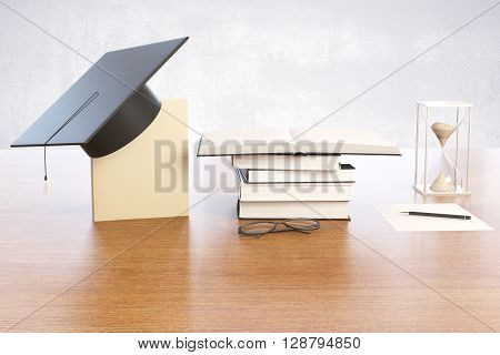 Graduation concept with book graduation cap hourglass and spectacles on wooden desktop with concrete wall in the background. 3D Rendering