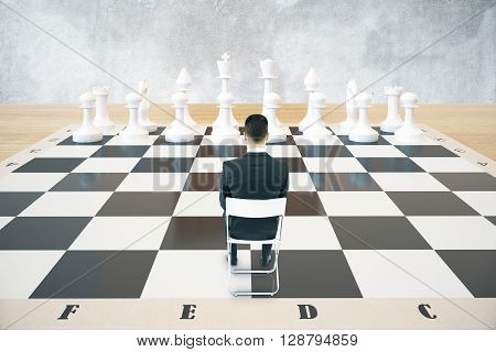 Strategy concept with sitting businessman and white chess pieces on huge chessboard with concrete wall in the background. 3D Rendering