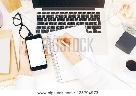 Closeup of woman hands copying data from white mock up smart phone to notepad on designer desktop with laptop and coffee cup. Business accountant working on report via cell phone on desktop. Mock up