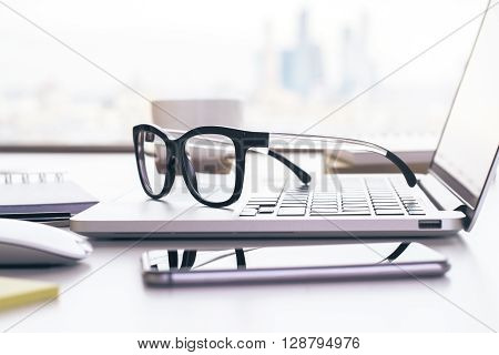 Closeup of glasses placed on laptop keyboard on office desktop with smart phone and business tools. Technology and office tools on desktop. Workplace concept