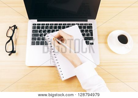 Top view of female hands writing in copybook on wooden table with glasses coffee and laptop with blank screen. Mock up
