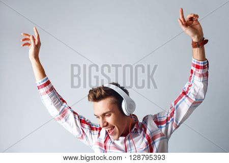 Handsome young man is dancing while listening to music. He is raising his arms up and smiling. The man is standing and wearing headphones. Isolated