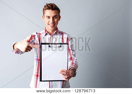 Waist up portrait of attractive young man showing a folder of documents. He is standing and pointing finger at it. The man is smiling. Isolated and copy space in right side