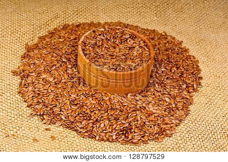 The flax seeds in a wooden bowl on canvas background