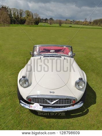 Saffron Walden, Essex, England - April 24, 2016: Classic white Daimler Dart SP250 Sports car on show parked on grass.