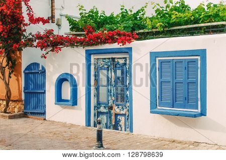 Facade of a very small white house with blue windows in Halkidiki Greece