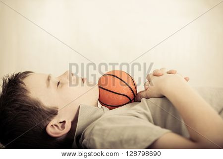 Child Asleep With Little Ball Under Chin