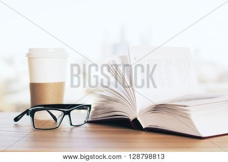 Open book glasses and coffee on wooden desk and blurry background
