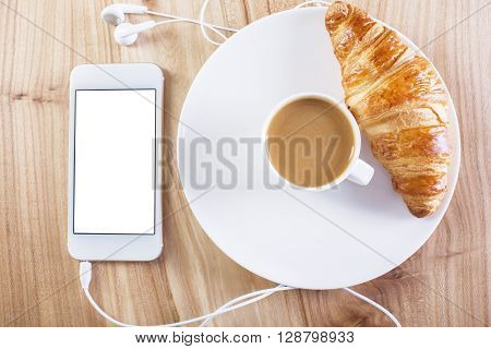 Topview of wooden desktop with blank white smartphone coffee and croissant. Mock up