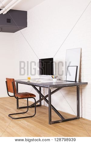 Sideview of brown chair and designer desk with computer monitor and picture frames on wooden floor and white brick wall background