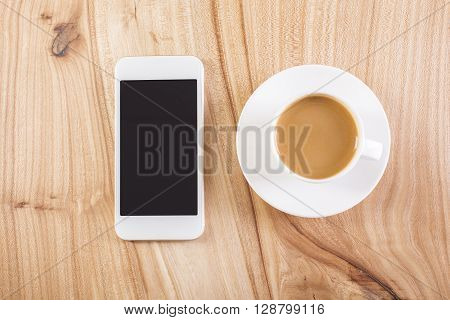 Topview of blank phone and coffee cup with saucer on natural wooden table. Mock up