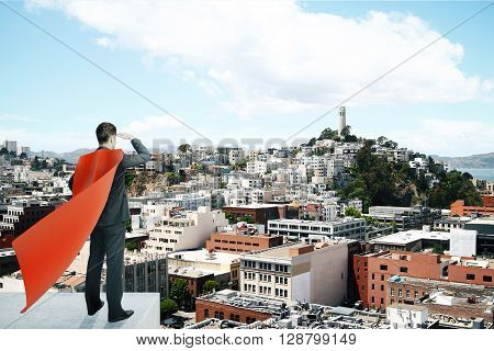 Businessman with red superhero cape standing on pedestal and looking into the distance on bright cityscape background