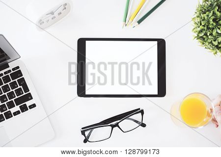 Topview of blank white tablet on office desktop with notebook glasses plant clock pencils and hand holding glass with orange juice. Mock up