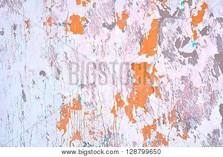 Textured grunge background - peeling light pink stucco and orange paint with blue streaks on the old rough wall surface. Architecture texture background.