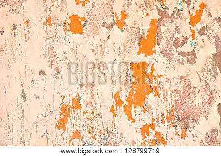 Textured retro background - peeling stucco of warm antique tones and orange chipped paint with blue spots on the old grunge wall surface. Architecture vintage background.