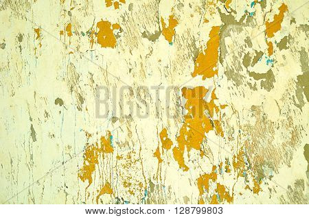 Textured vintage background - peeling light yellow stucco and chipped orange paint with blue streaks on the old wall surface. Architecture background.