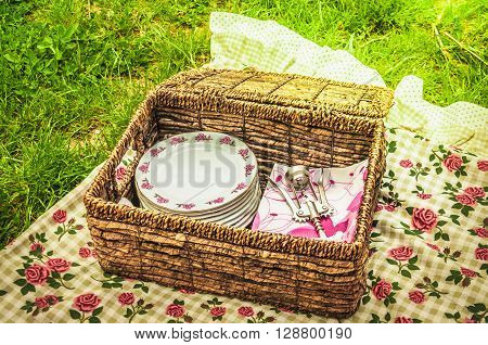 Picnic accessories, tablecloth and plates both decorated with roses