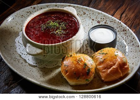 red borscht with sour cream, wild garlic, bread on a wooden background, rustic