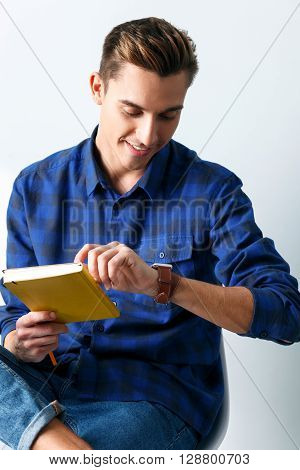 It is time to study now. Attractive young man is holding a notebook and pencil. He looking at smart watch with anticipation and smiling. Isolated