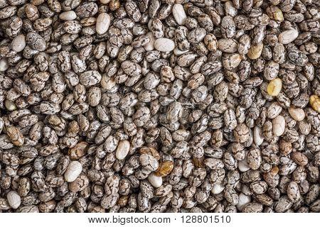 background of organic black chia seeds, life size macro