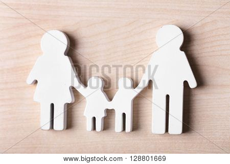 Cutout figurine of a family on wooden background