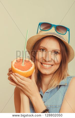 Happy glad woman tourist in straw hat and sunglasses holding grapefruit citrus fruit. Healthy diet food. Summer vacation holidays concept. Instagram filtered.