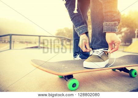 closeup of skateboarder tying shoelace at skatepark
