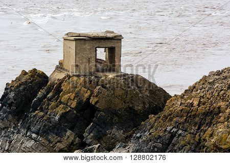 Abandoned defence post on British coast. A concrete gun station stands on rocks on the shore of the Bristol Channel, in Somerset, UK, part of an historic fort used in World War 2
