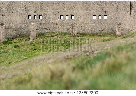 Concrete wall with ports for gunfire. Section of ruined fort on the Bristol Channel with stark military architecture appropriate for its defensive use