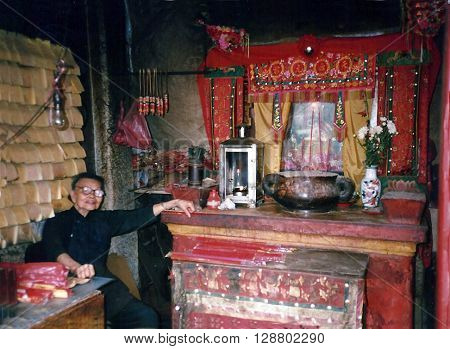 MACAU - CIRCA 1987: An elderly woman sits inside the A-Ma Temple, built in 1488, and dedicated to Matsu, the goddess of seafarers and fishermen.