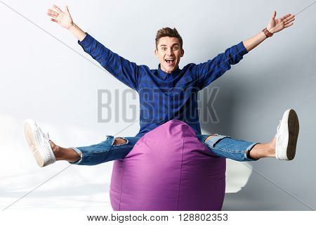 Cheerful young man is making fun on flexible soft chair. He is sitting and laughing. The man is stretching arms and legs. Isolated