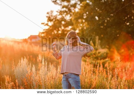 Portrait of young modern girl on the background of nature. Young woman  on a background sunset. Young woman in ripped jeans. in sun glasses