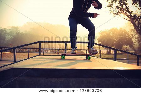 young woman skateboarder practice ollie at satepark
