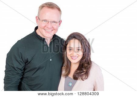 Happy smiling multiracial couple standing arm in arm looking at the camera with warm beaming friendly smiles isolated on white with copy space