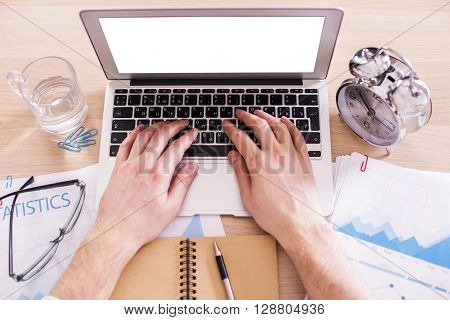 Topview of male hands typing on keyboard of laptop with blank white screen on office desk with glass of water and alarm. Mock up