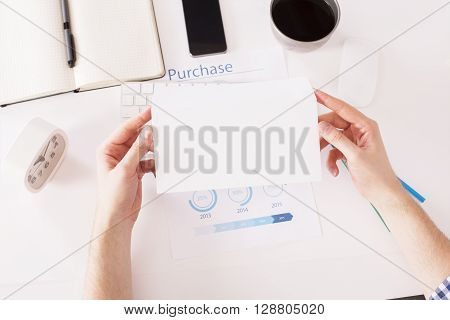 Hands holding regular blank envelope over office desktop with smartphone clock business report and other items. Topview Mock up