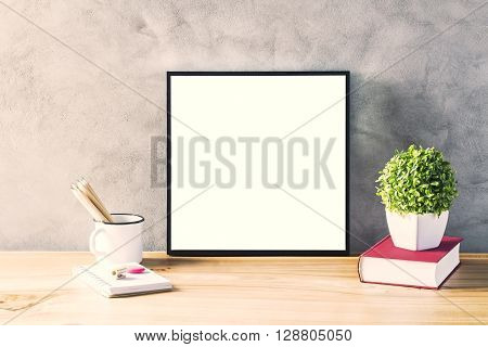 Closeup of wooden surface with blank frame flowerpot iron mug with pencils and glasses on concrete background. Mock up
