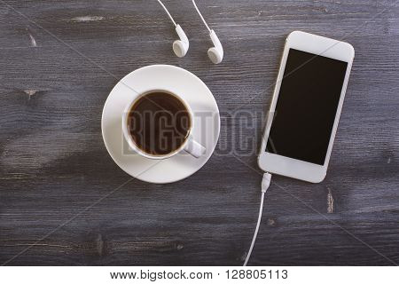 Topview of dark wooden desktop with coffee cup and saucer blank phone and headphones. Mock up