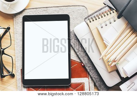 Topview of table with blank white tablet on case and office tools. Mock up