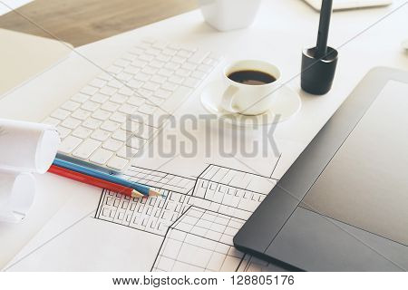 Closeup of tabletop with construction sketch graphic tablet coffee cup and other items
