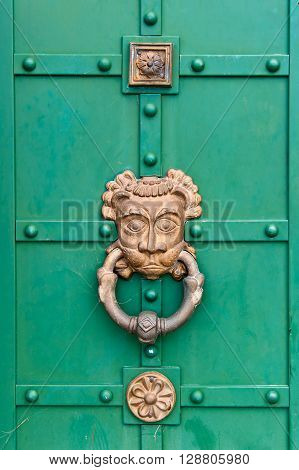ancient door with a large metal handle with large doorknocker like lion head