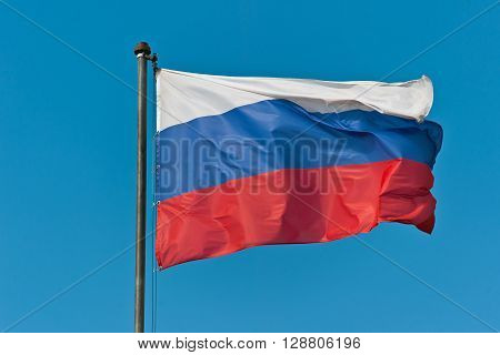 The flag of Russia developing in the wind on a flagpole in a windy day