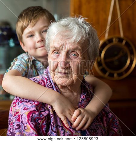 Portrait of an elderly woman, grandson at blurring in the background.