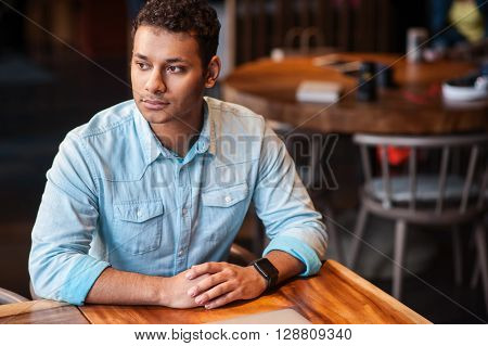 Cheerful Arabian man is sitting at table in cafe. He is looking forward pensively. The man is waiting with anticipation